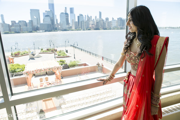 Sweet Indian bride looking at the amazing ceremony venue. in Jersey City, NJ Indian Wedding by Click Café Photography