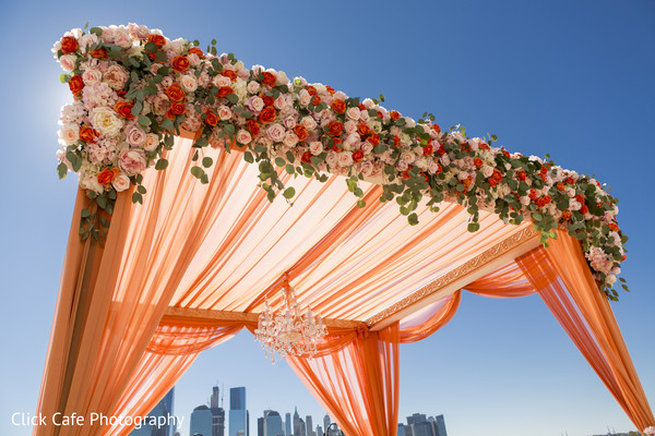 Beautiful orange mandap with an elegant crystal chandelier. in Jersey City, NJ Indian Wedding by Click Café Photography