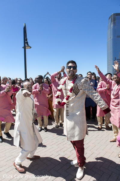 Indian groom dancing along with family and friends during traditional baraat. in Jersey City, NJ Indian Wedding by Click Café Photography