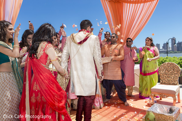 Family and friends throwing flower petals to the bride and groom. in Jersey City, NJ Indian Wedding by Click Café Photography