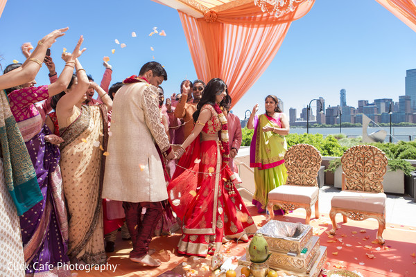 Family surrounding and throwing flower petals to the happy couple. in Jersey City, NJ Indian Wedding by Click Café Photography