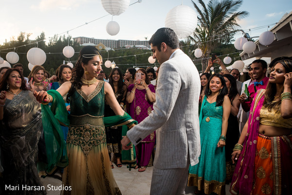 Indian bride and groom dancing at their pre-weeding beach party. in Southhampton, Bermuda Indian Wedding by Mari Harsan Studios