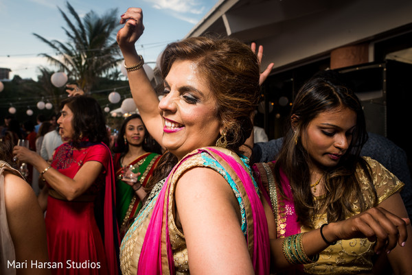 Party guest smiling and dancing at the beach party pre-wedding celebration. in Southhampton, Bermuda Indian Wedding by Mari Harsan Studios