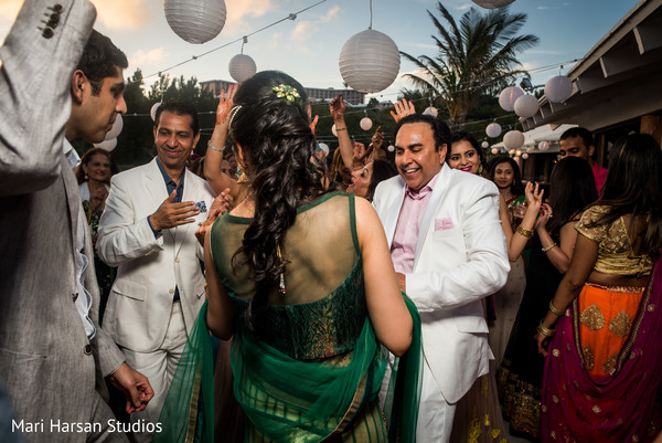 Bride and groom sharing and dancing at their pre-wedding beach party. in Southhampton, Bermuda Indian Wedding by Mari Harsan Studios