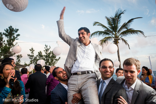 Indian Groomsmen carrying the groom on their shoulders. in Southhampton, Bermuda Indian Wedding by Mari Harsan Studios