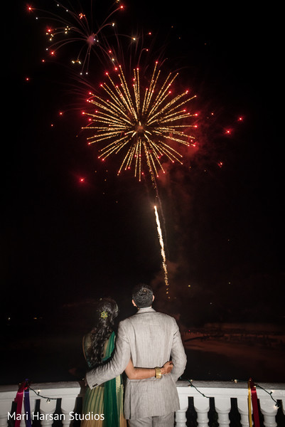 Sweet moment of bride and groom watching the fireworks. in Southhampton, Bermuda Indian Wedding by Mari Harsan Studios