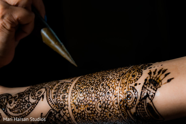 Mehndi artist giving the final touches to indian bridal mehndi design. in Southhampton, Bermuda Indian Wedding by Mari Harsan Studios