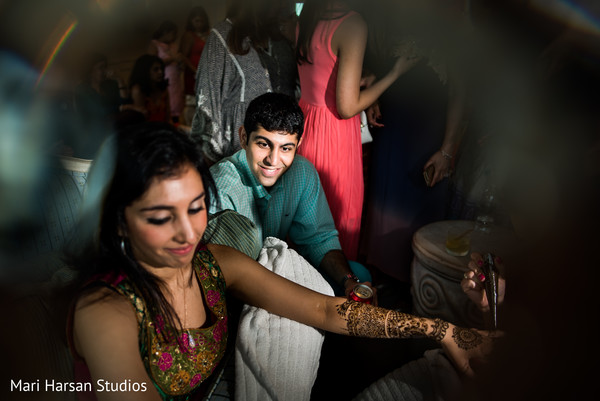 Family members watch how this indian bride gets her bridal mehndi done. in Southhampton, Bermuda Indian Wedding by Mari Harsan Studios