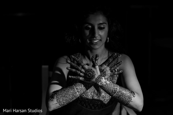 Indian bride with her intricate mehndi design. in Southhampton, Bermuda Indian Wedding by Mari Harsan Studios