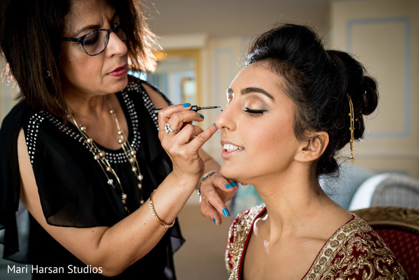 Make up artist adding the final touches to indian bride. in Southhampton, Bermuda Indian Wedding by Mari Harsan Studios