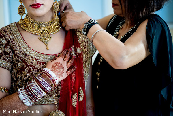 Indian bride getting her wedding attire adjusted. in Southhampton, Bermuda Indian Wedding by Mari Harsan Studios