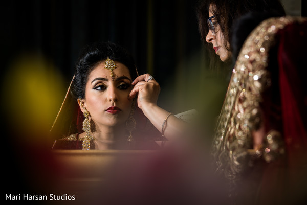 Make up artist giving the final touch ups to the lovely bride. in Southhampton, Bermuda Indian Wedding by Mari Harsan Studios