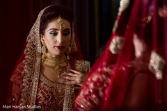 Indian bride checking her attire in the mirror.