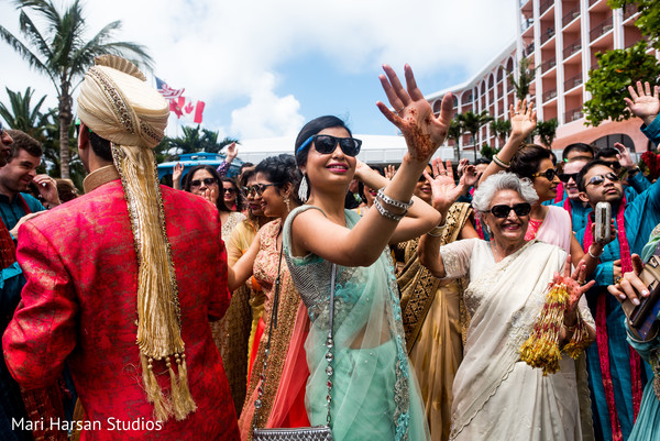 Relatives enjoying and sharing during the baraat. in Southhampton, Bermuda Indian Wedding by Mari Harsan Studios