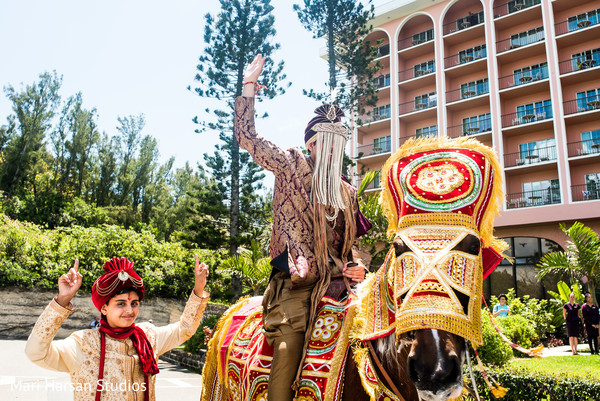 Indian groom riding the baraat horse. in Southhampton, Bermuda Indian Wedding by Mari Harsan Studios