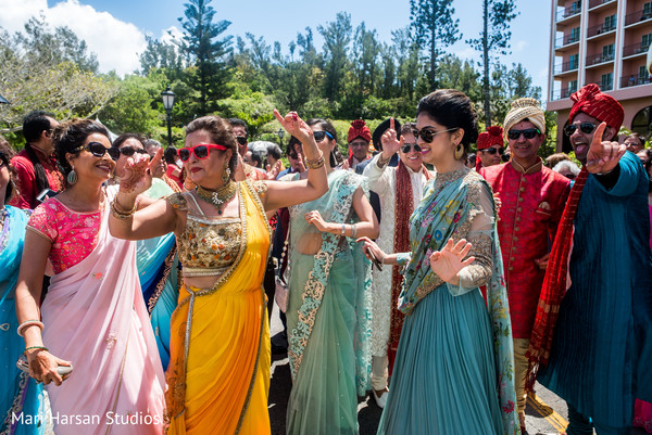 Family and friends escorting the groom's baraat. in Southhampton, Bermuda Indian Wedding by Mari Harsan Studios