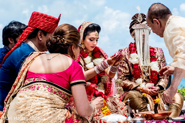 Indian bride and groom in their wedding ceremony. in Southhampton, Bermuda Indian Wedding by Mari Harsan Studios