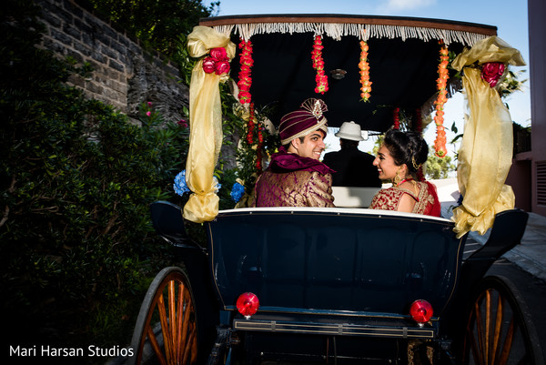 Indian bride and groom leaving the wedding ceremony in an elegant horse-carriage. in Southhampton, Bermuda Indian Wedding by Mari Harsan Studios