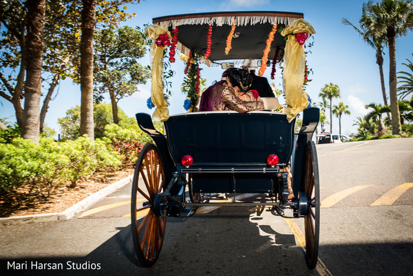 Sweet moment of indian bride and groom leaving the wedding ceremony. in Southhampton, Bermuda Indian Wedding by Mari Harsan Studios