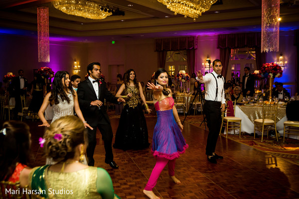 Guests performing at the wedding reception. in Southhampton, Bermuda Indian Wedding by Mari Harsan Studios