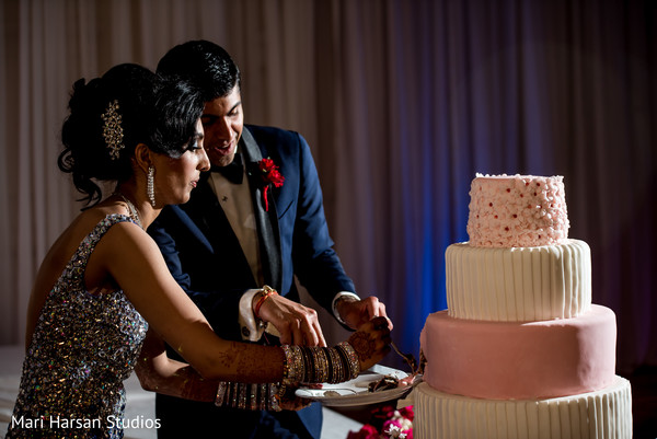 Indian bride and groom cutting their wedding cake. in Southhampton, Bermuda Indian Wedding by Mari Harsan Studios