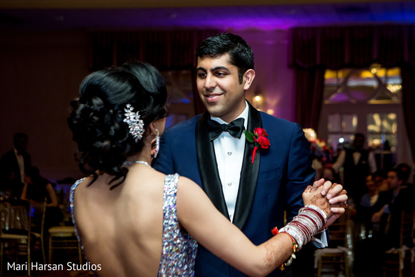 Indian groom dancing with his lovely bride. in Southhampton, Bermuda Indian Wedding by Mari Harsan Studios