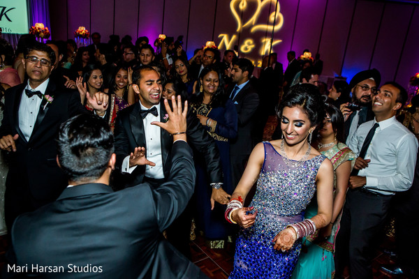 Friends and family dancing along with the bride and groom. in Southhampton, Bermuda Indian Wedding by Mari Harsan Studios