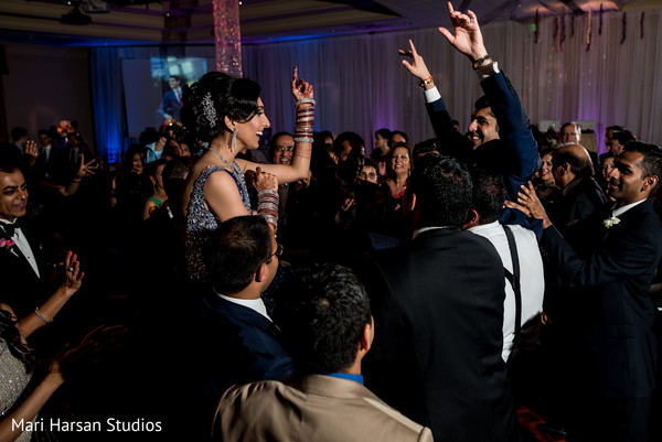 Indian bride and groom got carried on the shoulders of their guests during their wedding. in Southhampton, Bermuda Indian Wedding by Mari Harsan Studios