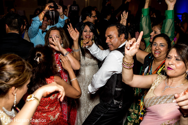 Guests dancing and celebrating at the wedding reception. in Southhampton, Bermuda Indian Wedding by Mari Harsan Studios