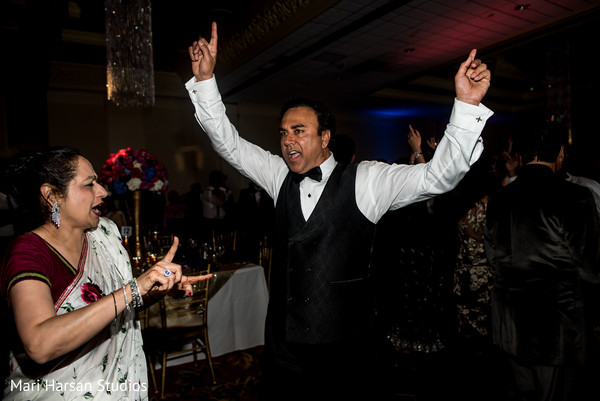 Indian wedding guests dancing at the reception party. in Southhampton, Bermuda Indian Wedding by Mari Harsan Studios