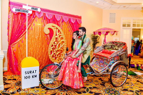 Indian bride and groom riding a colorful rickshaw. in Edison, NJ Indian Wedding by House of Talent Studio