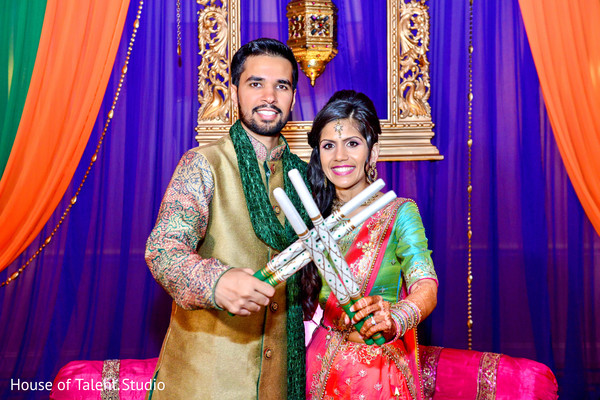 Indian bride and groom ready to dance with their garba sticks. in Edison, NJ Indian Wedding by House of Talent Studio
