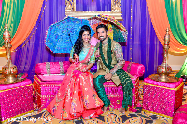 Indian bride and groom posing with colorful umbrellas. in Edison, NJ Indian Wedding by House of Talent Studio
