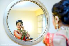 Indian bride adjusting her jewelry.