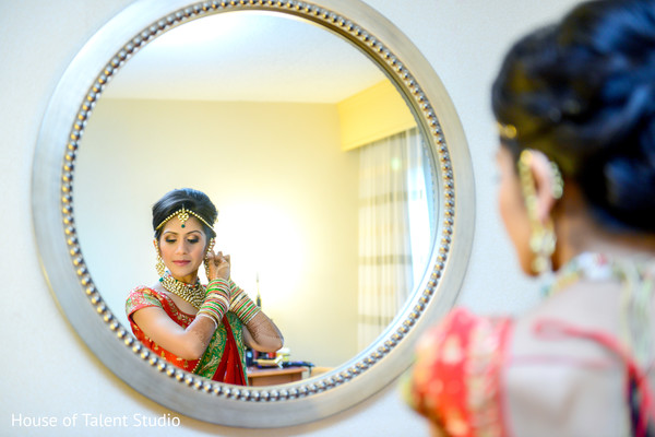 Indian bride adjusting her jewelry. in Edison, NJ Indian Wedding by House of Talent Studio