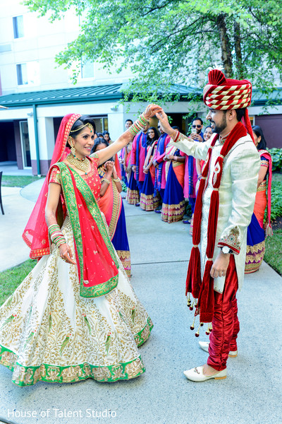 Indian bride in traditional white red and gren lengha with groom in red and white sherwani. in Edison, NJ Indian Wedding by House of Talent Studio