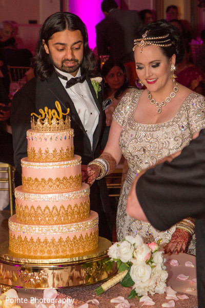 Lovely couple cutting their wedding cake in Detroit, Michigan Fusion Wedding by Pointe Photography