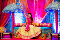 Beautiful indian bride posing in a colorful sangeet stage.