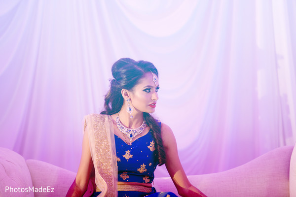 Stunning indian bride seating in the main stage at the wedding reception.