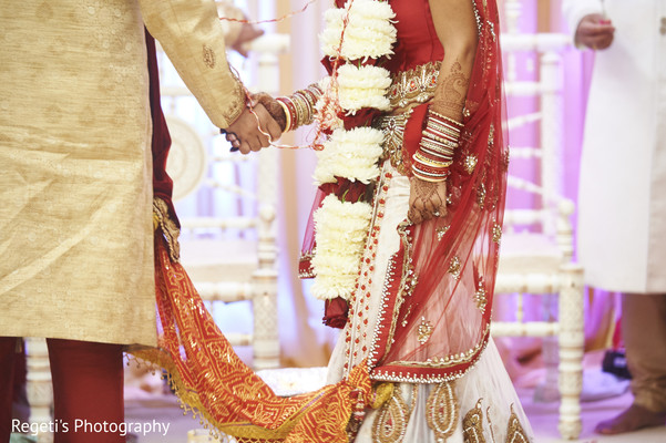 Indian couple holding hands during the wedding ceremony. in Herndon, VA Indian Wedding by Regeti's Photography