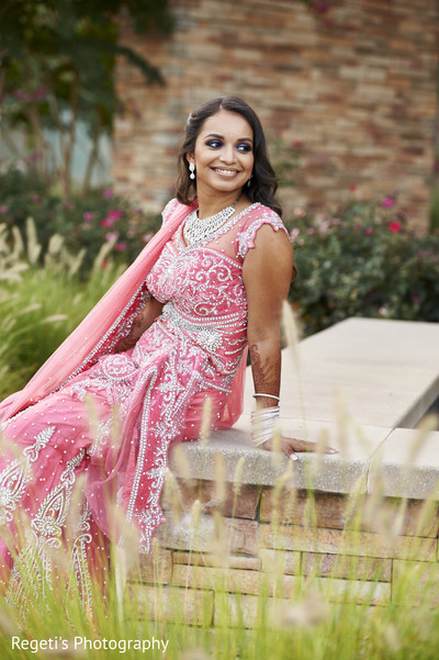 Beautiful indian bride in a silver and coral reception lengha. in Herndon, VA Indian Wedding by Regeti's Photography