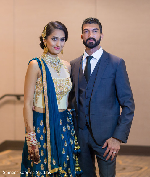 Indian Bride In Reception Lengha And Groom In A Deep Blue Suit
