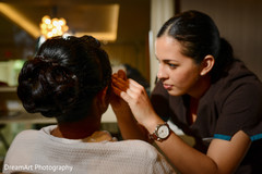 Makeup artist giving the final touch ups to the bride