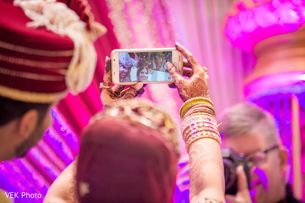 Indian bride and groom taking a selfie picture.