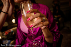 Indian bride drinking champagne while getting ready.