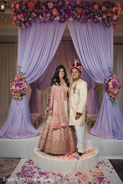 Beautiful indian couple under a purple flower mandap