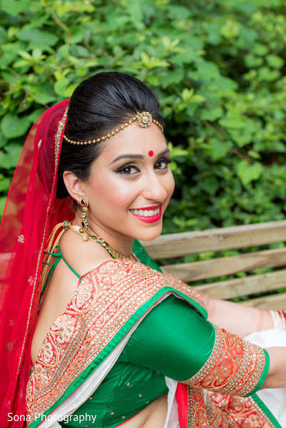Indian bride in red and green ceremony attire.