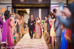 indian bride walking down the aisle with father