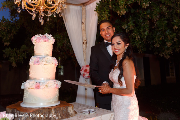 Indian bride and groom with their 3 tier wedding cake