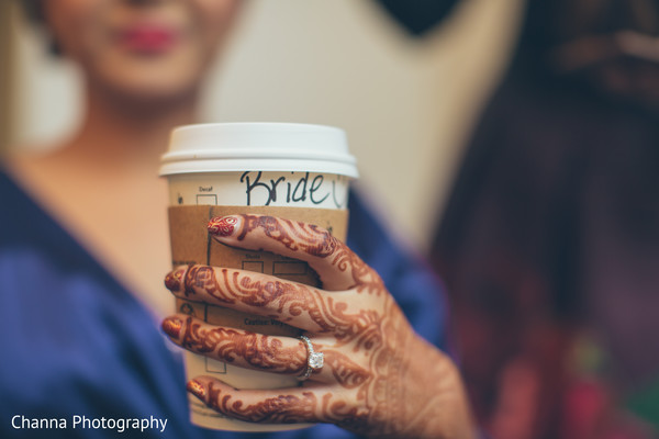 Indian bride drinking coffee while getting ready .
